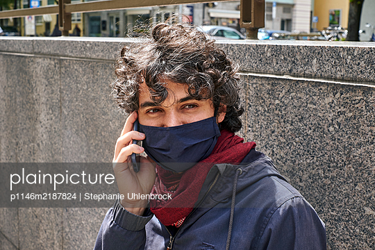 Man wearing facial mask using smartphone, portrait - p1146m2187824 by Stephanie Uhlenbrock