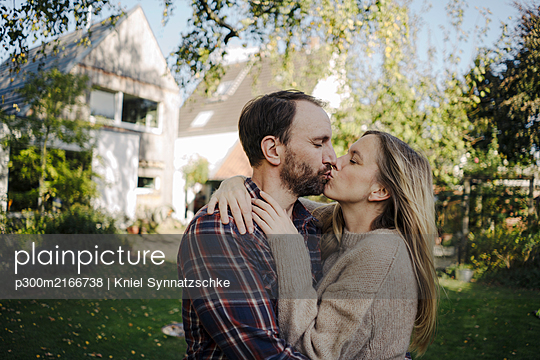 Happy couple kissing in garden, in front of their dream house - p300m2166738 by Kniel Synnatzschke