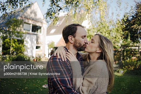 Happy couple kissing in garden, in front of their dream house - p300m2166738 von Kniel Synnatzschke