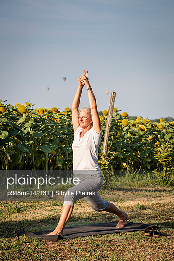 Woman doing yoga in front of a sunflower field - p948m2142131 by Sibylle Pietrek