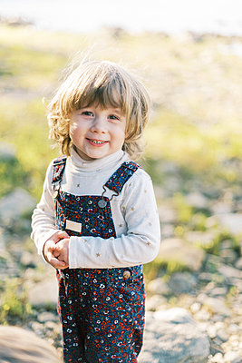A little toddler girl with a big smile looking into the camera - p1166m2208560 by Cavan Images