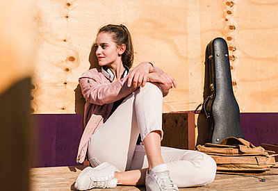 Relaxed young woman sitting on platform next to guitar case and bag - p300m2059617 by Uwe Umstätter