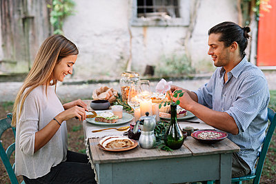 Couple having a romantic candelight meal next to a cottage - p300m2068816 von Alberto Bogo