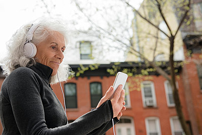 Older woman listening to cell phone with headphones in city - p555m1491484 by JGI/Jamie Grill