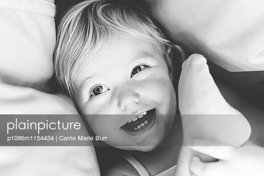 Kleines Mädchen spielt mit ihrem Fuß - p1086m1154434 von Carrie Marie Burr