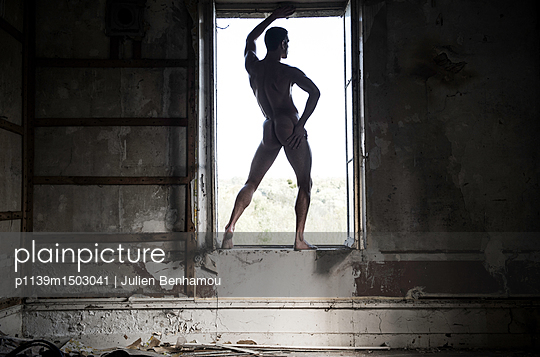 Young man poses naked in open window - p1139m1503041 by Julien Benhamou
