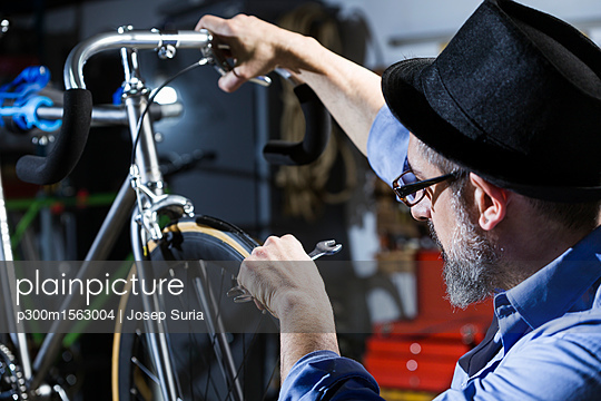 Man working on bicycle in workshop - p300m1563004 by Josep Suria