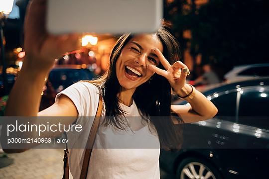 Young woman using smartphone in the city at night, taking a selfie - p300m2140969 by alev