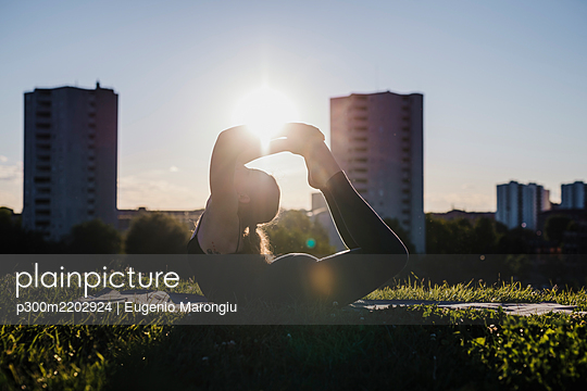 Young woman performing yoga in bow pose at city park during sunny day - p300m2202924 by Eugenio Marongiu