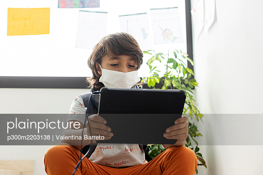 Boy wearing face mask using digital tablet while sitting in school - p300m2203138 by Valentina Barreto