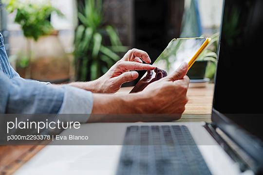 Male freelancer using digital tablet at backyard - p300m2293378 by Eva Blanco