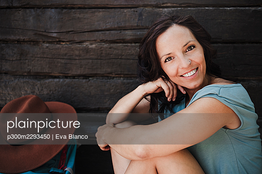 Happy female tourist sitting in front of cottage - p300m2293450 by Eva Blanco