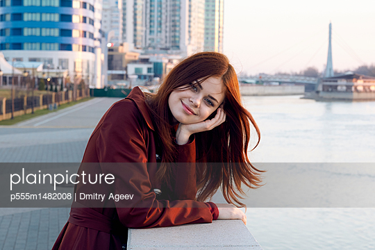 Smiling Caucasian woman leaning on wall at waterfront - p555m1482008 by Dmitry Ageev