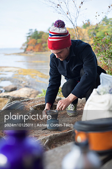 Male hiker igniting camping stove on riverbank, Rangeley, Maine, USA