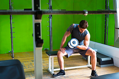 Man lifting dumbbell while sitting on seat against green wall in gym - p1166m2060749 by Cavan Social