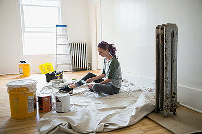 Woman viewing paint swatches on drop cloth in living room - p1192m1158279 by Hero Images