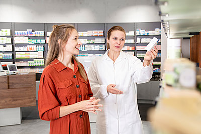 Female pharmacist assisting woman with prescription at store - p300m2251307 by Florian Küttler
