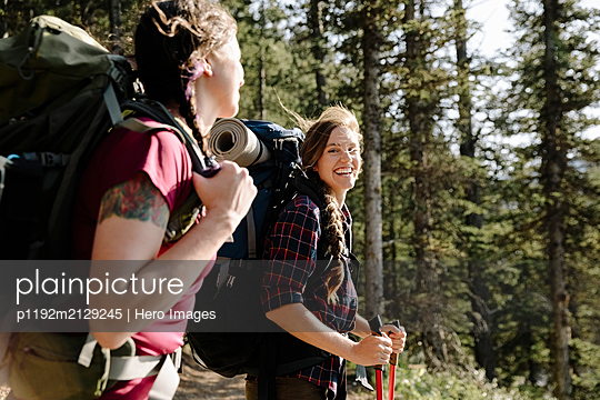 Happy female backpacker friends hiking in sunny woods - p1192m2129245 by Hero Images