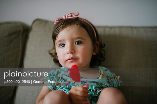 Cute baby girl eating a heart shaped lollipop at home - p300m2012540 von Gemma Ferrando