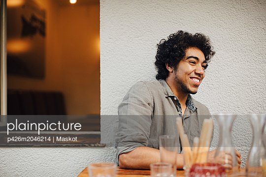 Smiling young man looking away while sitting at table against wall - p426m2046214 by Maskot
