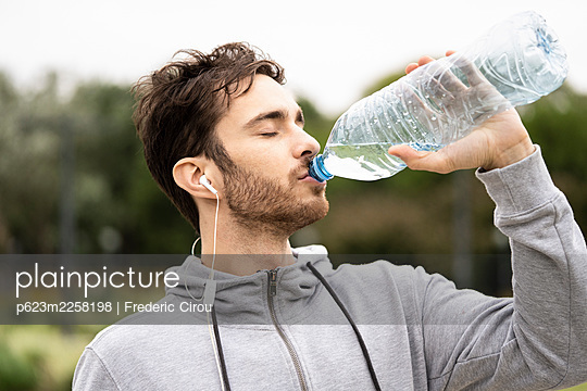 Young man drinking water - p623m2258198 by Frederic Cirou