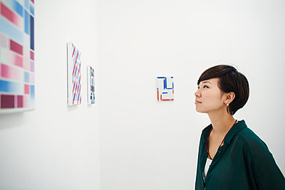 Woman with short black hair wearing green shirt standing in art gallery, looking at modern painting. - p1100m1531071 by Mint Images