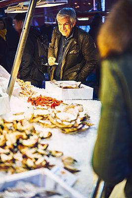 Mann mit Geldschein steht an einem Marktstand mit Krabben in Venedig - p1312m2082187 von Axel Killian