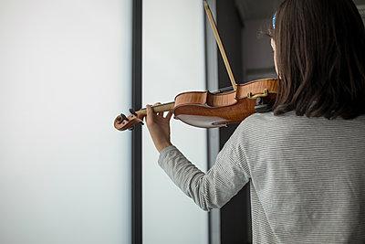 Rear view of schoolgirl playing violin in music school - p1315m2003047 by Wavebreak