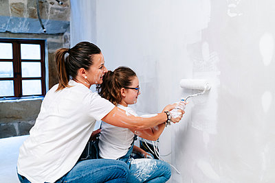 Mother and daughter painting a wall of her new house together - p300m2166535 by Daniel González