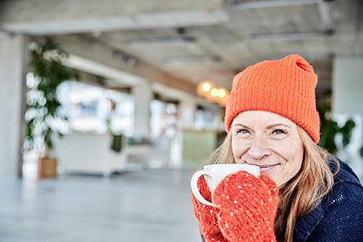 Smiling woman having coffee at loft apartment - p300m2265225 by Jo Kirchherr