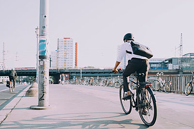 Rear view of businessman riding bicycle on sidewalk against clear sky in city - p426m2169596 by Maskot