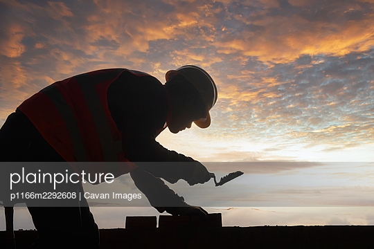 Silhouette construction mason worker bricklayer - p1166m2292608 by Cavan Images