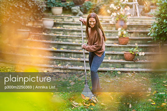 Smiling woman sweeping with rake in garden - p300m2250369 by Annika List
