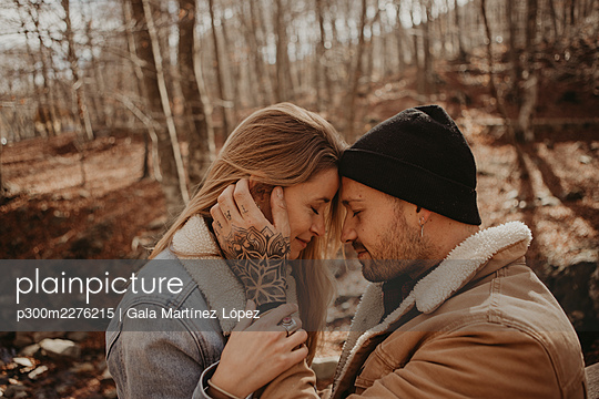 Affectionate mid adult couple in forest during autumn - p300m2276215 by Gala Martínez López