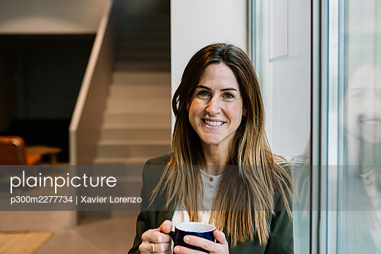 Smiling businesswoman with coffee mug leaning on glass window at office - p300m2277734 by Xavier Lorenzo