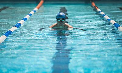 Young Caucasian male swimmer swimming butterfly stroke in swimming pool - p1315m2091024 by Wavebreak