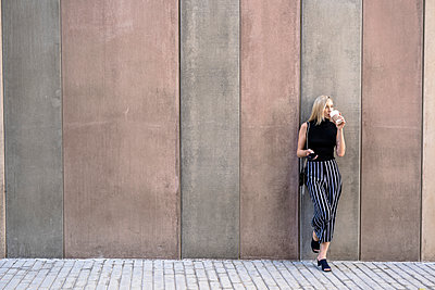 Young blond woman with cell phone leaning against wall drinking coffee to go - p300m2102985 by Giorgio Fochesato
