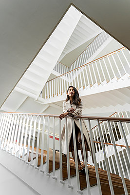 Young woman standing in staircase - p300m2166199 by VITTA GALLERY