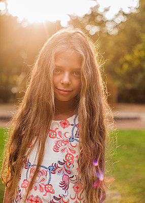 Cute girl standing at public park during sunset - p300m2239987 by LOUIS CHRISTIAN