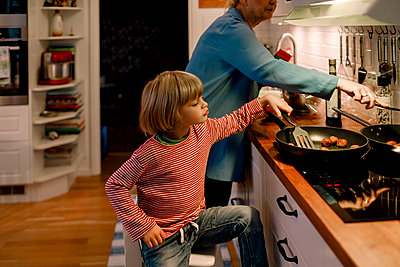 Boy helping grandmother in cooking food at home - p426m2195346 by Maskot