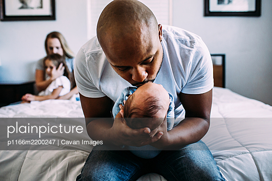 dad kissing newborn on bed with mom and daughter in back ground - p1166m2200247 by Cavan Images