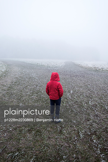 Small boy alone in a red jacket - p1228m2230869 by Benjamin Harte
