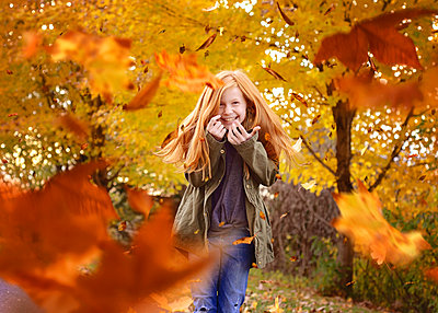 Beautiful Red Haired Girls in Falling Autumn Leaves - p1166m2147583 by Cavan Images