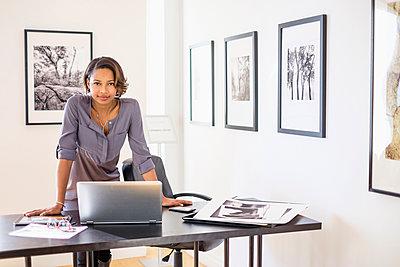 Black woman using laptop in art gallery office - p555m1305057 by JGI/Tom Grill