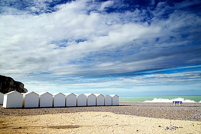 White beach huts in a row on shingle beach - p924m806959f by Still Factory