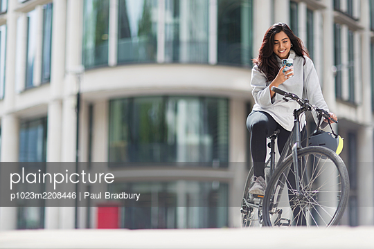Smiling woman using smart phone on bicycle in sunny city - p1023m2208446 by Paul Bradbury