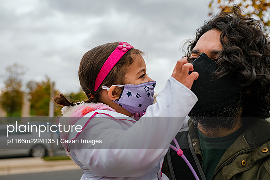 Little girl in halloween costume with dad wearing protective face mask - p1166m2224135 by Cavan Images