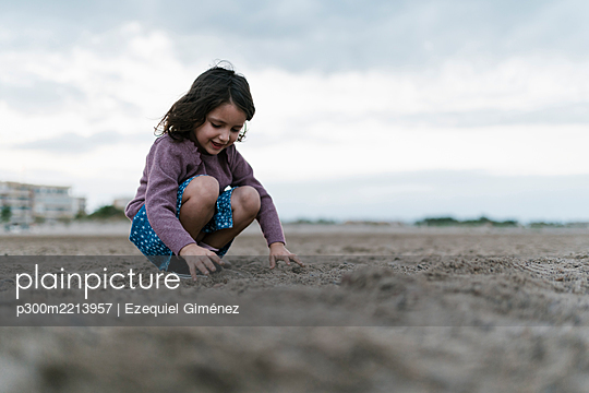 Smiling girl playing with sand while crouching at beach against cloudy sky - p300m2213957 by Ezequiel Giménez