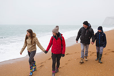 Family in warm clothing walking on snowy winter beach - p1023m2024360 by Sam Edwards