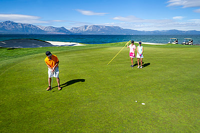 Three people playing golf at Edgewood Tahoe in Stateline, Nevada. - p1166m2192095 by Cavan Images